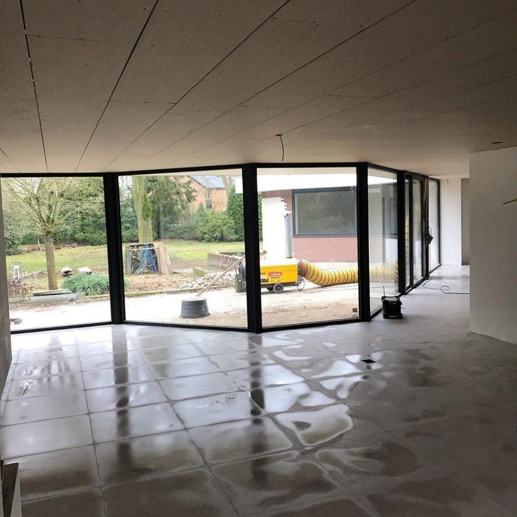 Betonlook tegels laten leggen in grote ruimte
